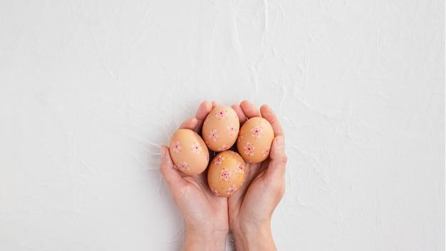 Вид сверху рук, держащих украшенные пасхальные яйца