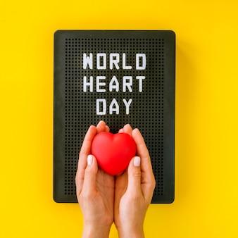 Вид сверху на руки, держащие сердце на всемирный день сердца