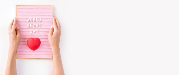 コピースペースで世界のハートの日のハートの形を保持している手のトップビュー