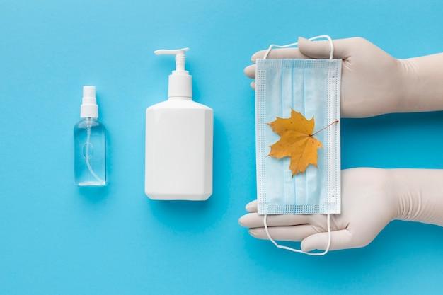 Вид сверху на руки, держащие медицинскую маску с осенним листом и бутылку с жидким мылом
