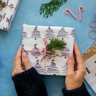 Вид сверху на руки, держащие завернутый рождественский подарок