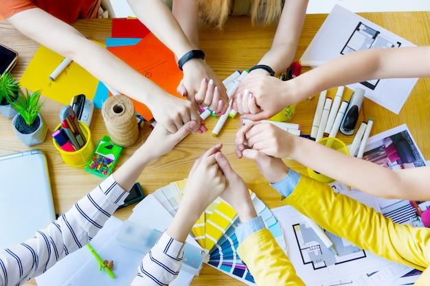 クリエイティブ・オフィスの机の上にお互いの手を繋いでいるビジネス人々の手の平面図です。色見本、部屋のレイアウト、備品を備えたテーブルにいる建築家やインテリアデザイナー。チームワークの概念。