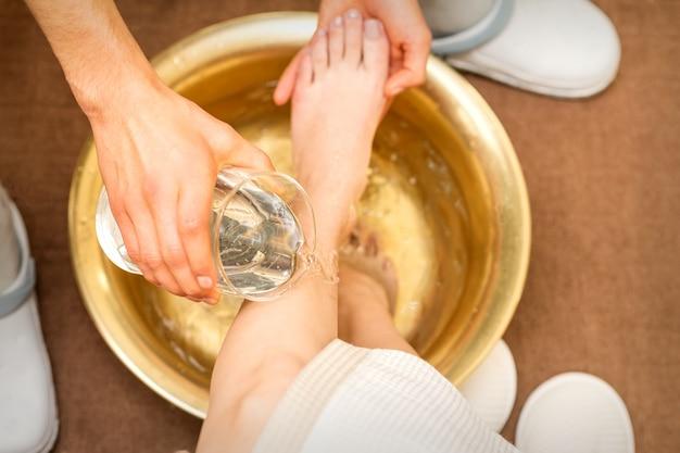 뷰티 스파 살롱에서 황금 그릇에 젊은 여자의 다리를 세척하는 안마사의 손의 상위 뷰