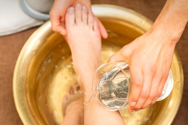 뷰티 스파 살롱에서 황금 그릇에 젊은 여성의 다리를 씻는 안마사의 손의 상위 뷰