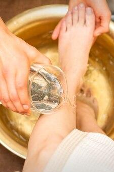 뷰티 스파 살롱에서 황금 그릇에 젊은 여성의 다리를 씻는 안마사의 손의 상위 뷰.