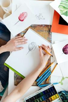 テーブルでチューリップbuゲルインクペンを描く女性画家の手の上面図