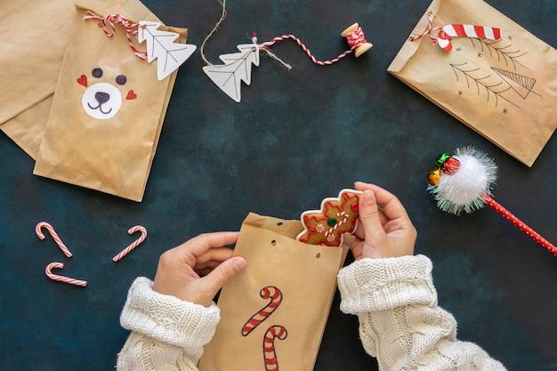 Вид сверху руки кладут угощения в рождественские подарочные пакеты