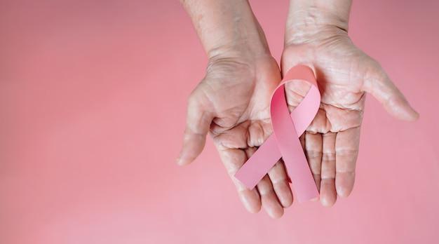 Вид сверху на руки, поддерживающие день борьбы с раком молочной железы, держа розовую ленту осведомленности о раке молочной железы