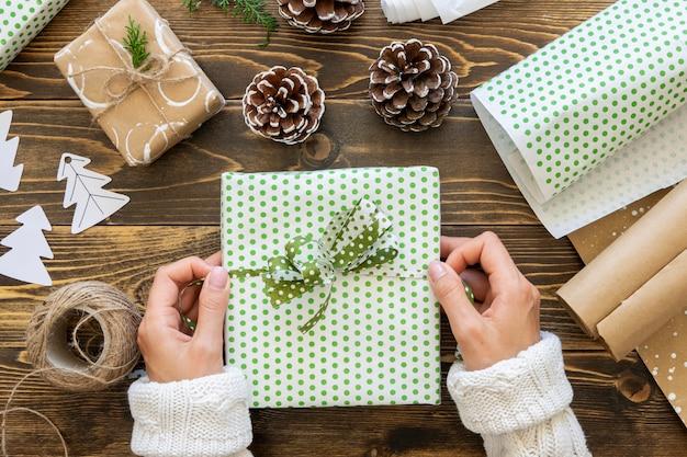 Вид сверху на руки, связывающие рождественский подарок веревкой
