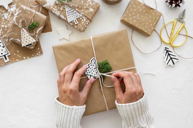 Вид сверху рук, связывающих рождественские подарки