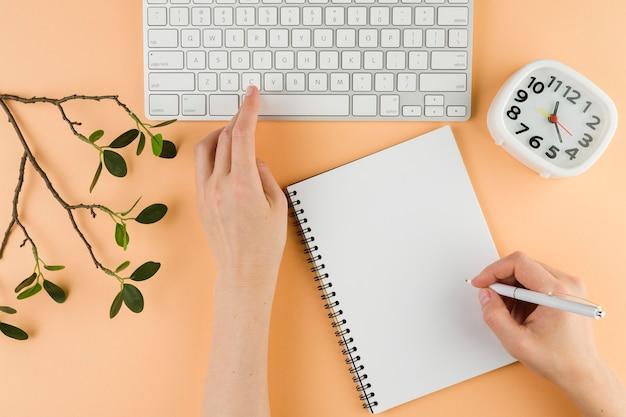 Взгляд сверху рук с тетрадью на столе и клавиатуре