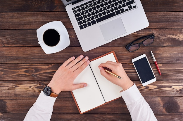 オフィスのテーブルにメモ帳、ラップトップ、電話、ペン、メガネで書いている手の上面図。