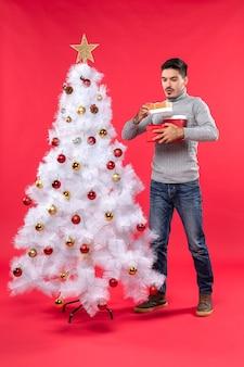 장식 된 화이트 크리스마스 트리 근처에 서있는 회색 블라우스에 잘 생긴 성인의 상위 뷰