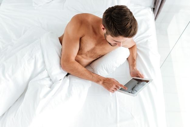 Вид сверху красивого молодого человека, лежащего в постели и использующего планшет