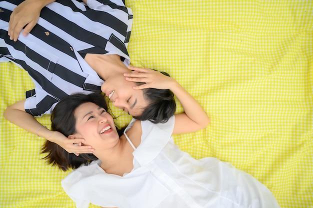 黄色い布の上に横たわって楽しい時間を過ごしている愛の幸せなアジアのlgbtカップルの上面図
