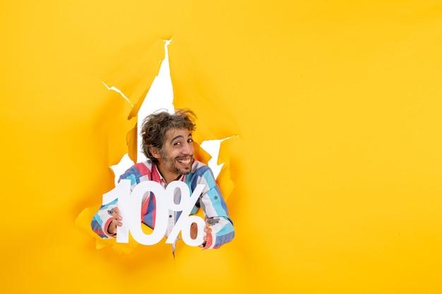 黄色い紙の引き裂かれた穴に10パーセントを示す幸せなひげを生やした男の上面図