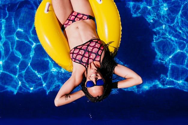 スイミングプールで膨らませて黄色のドーナツに浮かぶ幸せな白人女性の上面図。夏の時間、休暇、ライフスタイル
