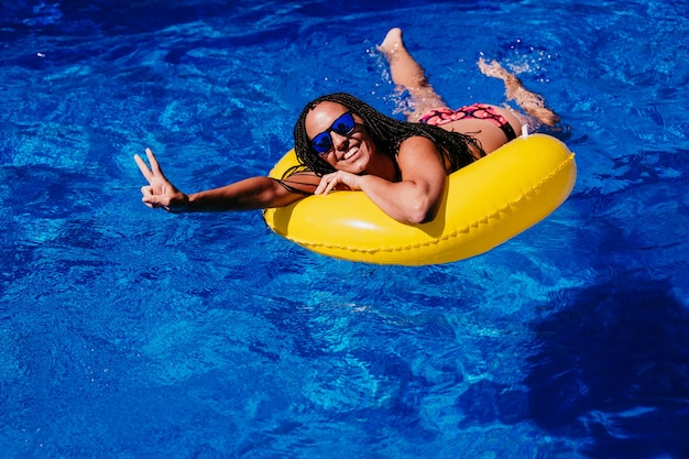 スイミングプールで膨らませて黄色のドーナツでリラックスして幸せな白人女性の上面図。手でvサインを作成します。夏の時間、休暇、ライフスタイル