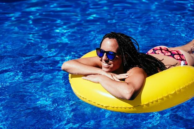 スイミングプールで膨らませて黄色のドーナツでリラックスして幸せな白人女性の上面図。夏の時間、休暇、ライフスタイル
