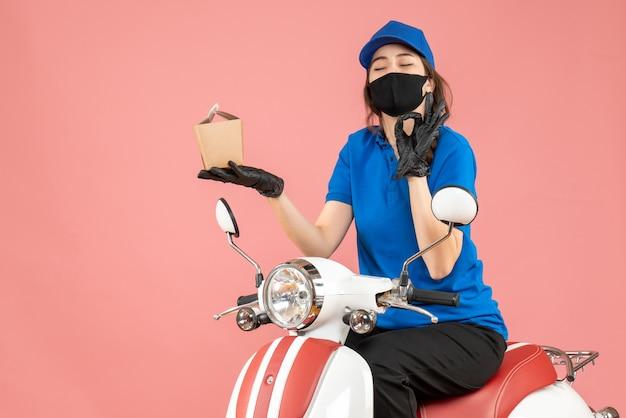 パステル調の桃の背景に注文を配達するスクーターに座って医療用マスクと手袋を着た幸せな配達人のトップビュー