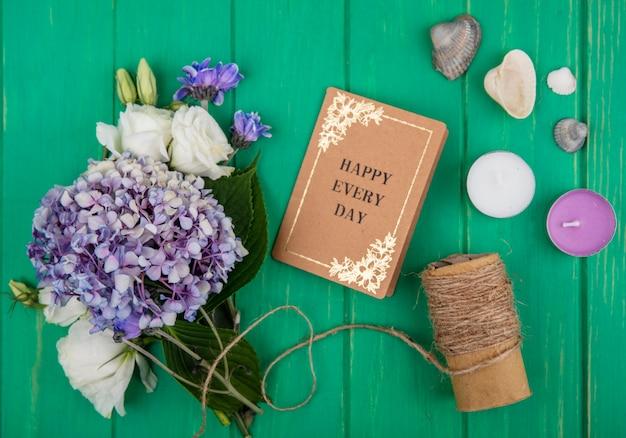 Вид сверху счастливой повседневной открытки и цветов, связывающих свечи с цветочными лепестками на зеленом фоне
