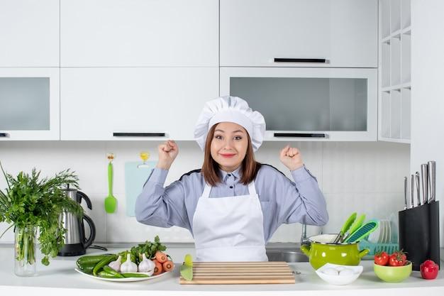 幸せな女性シェフと調理器具と白いキッチンで新鮮な野菜の上面図