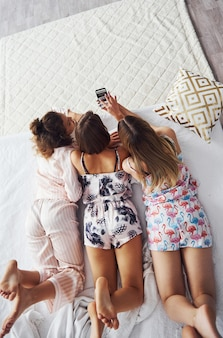 Вид сверху счастливых подруг, которые лежат на кровати и хорошо проводят время на пижамной вечеринке в спальне.