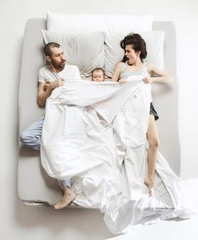 Вид сверху счастливой смешной семьи с одним новорожденным ребенком в спальне. нам нравится быть вместе. счастливая семья в постели. вид сверху. концепция эмоций. утро после сна. семейный образ жизни. концепция счастливых родителей