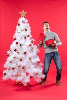 飾られた白いクリスマスツリーの近くに立っている灰色のブラウスで幸せなハンサムな大人の上面図