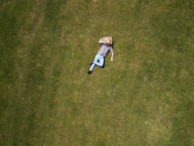 Взгляд сверху счастливого человека лежа на зеленой траве