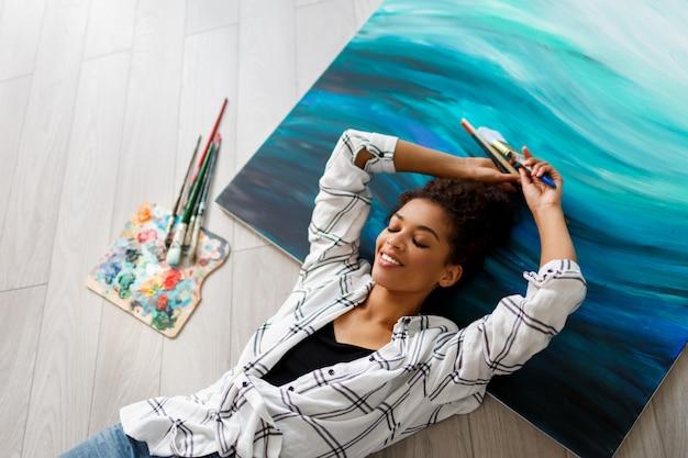 Взгляд сверху счастливой женщины африканца художника африканской лежа на холсте и смотря камеру с щетками в руках.