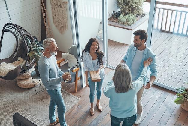 Вид сверху счастливых пожилых родителей, встречающих молодую пару внутри дома