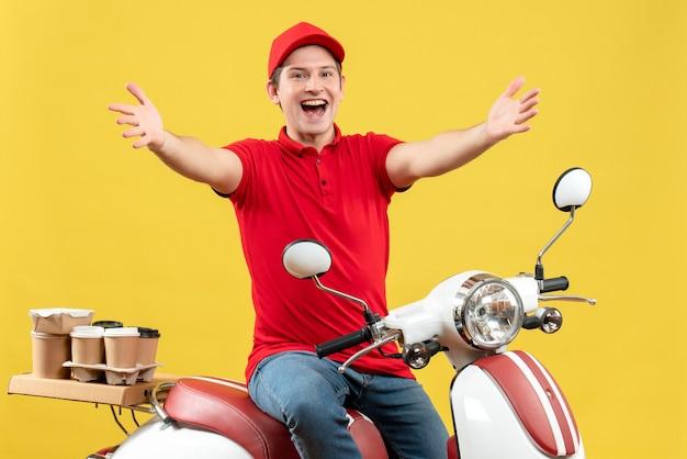 赤いブラウスと帽子を身に着けている幸せな若い大人の平面図黄色の背景に腕を前方に伸ばしてスクーターに座って注文を配信します。