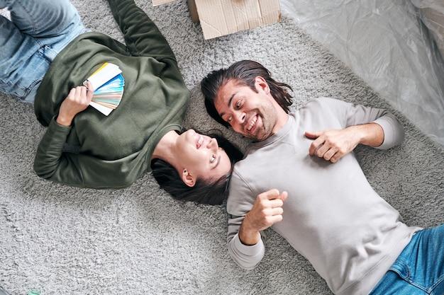 Вид сверху счастливой молодой влюбленной пары, лежащей на полу в своем новом доме или квартире после удаления и обсуждения идей