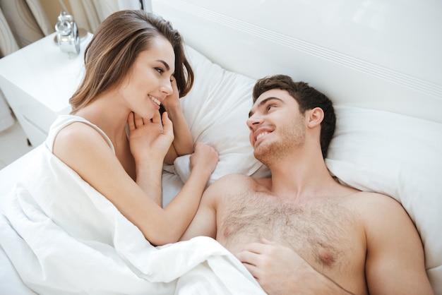 Вид сверху счастливой молодой пары, лежа и улыбаясь в постели вместе