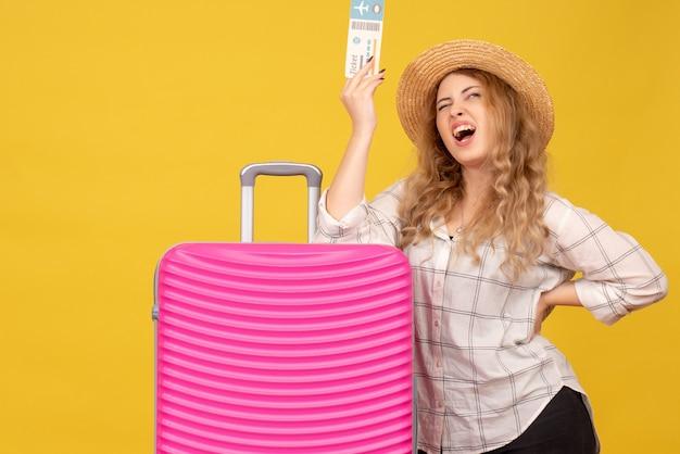 Вид сверху счастливой молодой леди в шляпе, держащей билет и стоящей рядом со своей розовой сумкой