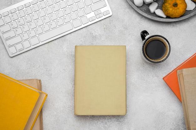 コーヒーとキーボードと机の上のハードカバーの本の上面図