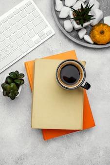 コーヒーと植物と机の上のハードカバーの本の上面図