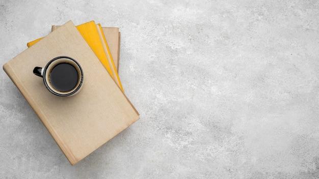 コーヒーとコピースペースのあるテーブルの上のハードカバーの本の上面図