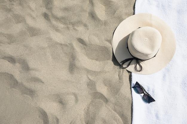 ビーチタオルの上に帽子のトップビュー Premium写真