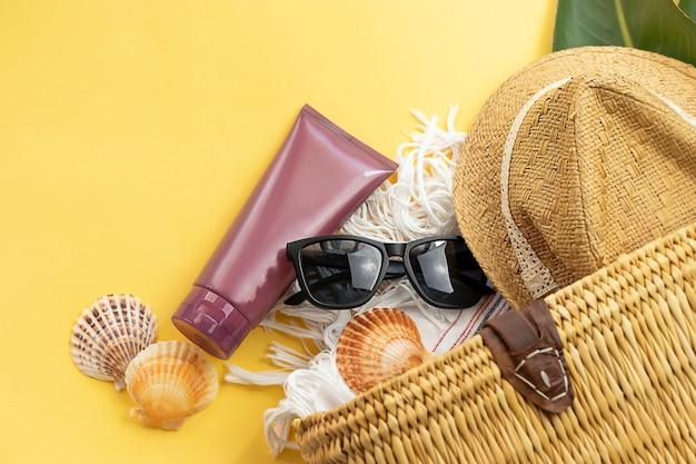 노란색 벽에 모자 태양 안경 자외선 차단제 크림과 비치 가방의 상위 뷰