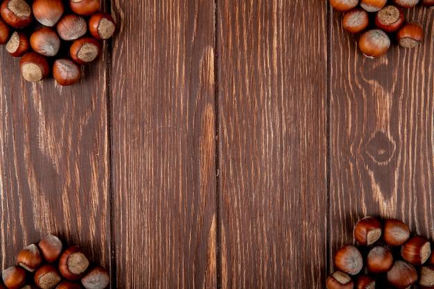 コピースペースを持つ木製の背景上のシェルでヘーゼルナッツのトップビュー