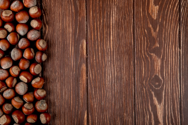 コピースペースを持つ木製の背景に散在しているシェルのヘーゼルナッツのトップビュー