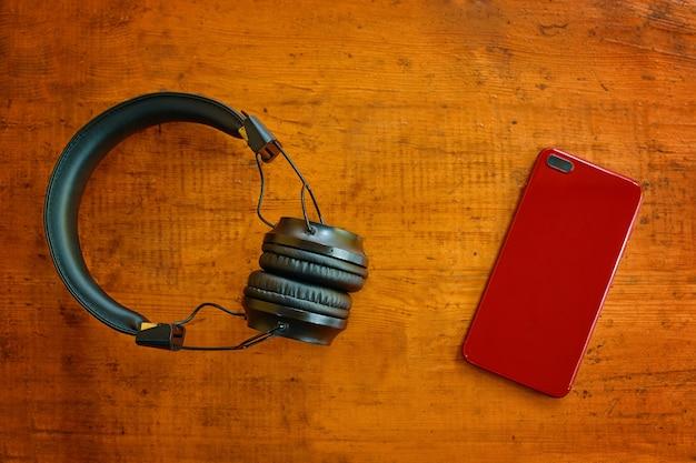 木製のテーブルの上のヘッドフォンとスマートフォンの上面図赤い携帯電話と黒いイヤホンのインスタグラムブログ
