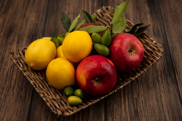 Вид сверху на полезные фрукты, такие как яблоки, лимоны и кинканы, на плетеном подносе на деревянной поверхности