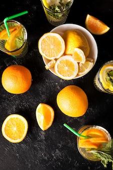 짙은 빈티지 나무 판자에 자른 과일 옆에 있는 건강하고 맛있는 레모네이드와 오렌지에이드의 최고 전망