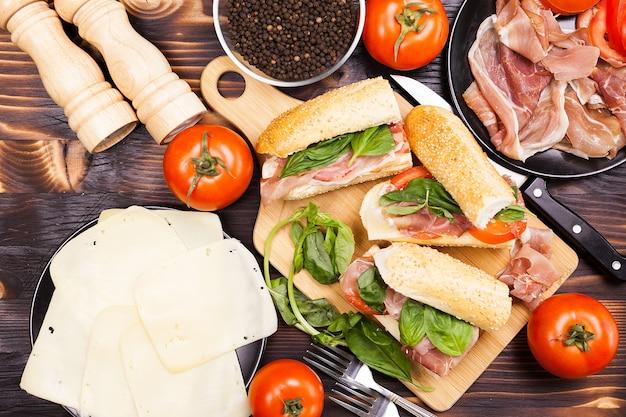 Вид сверху здоровых и вкусных бутербродов на деревянной доске рядом с помидорами, ветчиной и сыром