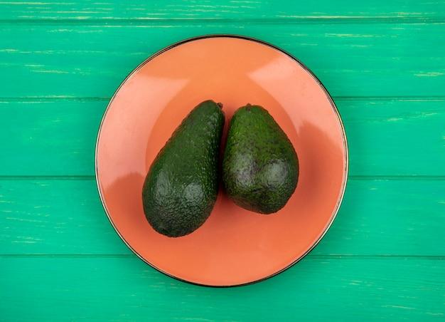 緑の表面のオレンジプレートに健康的で新鮮なアボカドのトップビュー