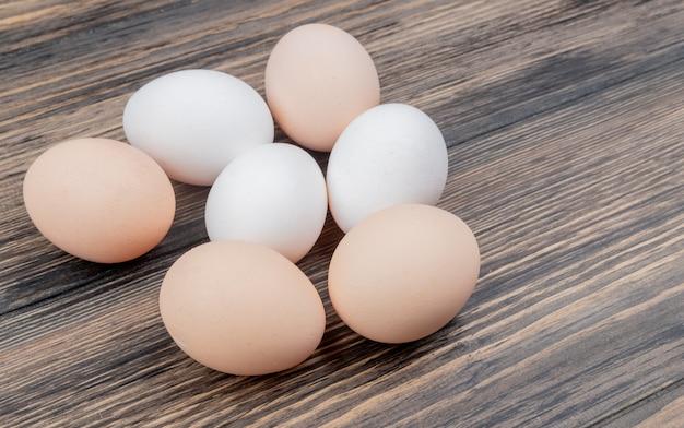 Вид сверху здоровых и свежих куриных яиц, изолированных на деревянном фоне