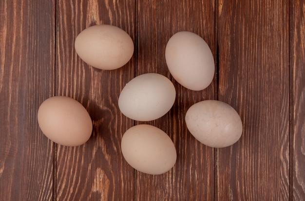 Вид сверху здоровых и свежих яиц, изолированных на деревянном фоне